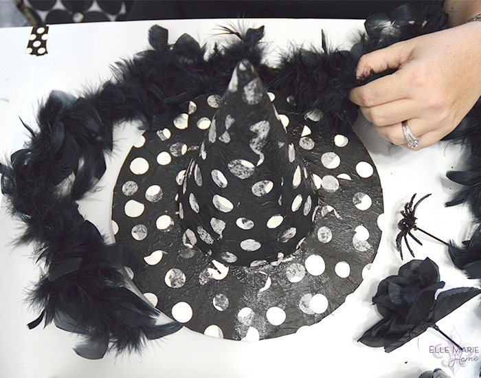 Decorating decoupage witch hat with black feather boa and black rose and black spider