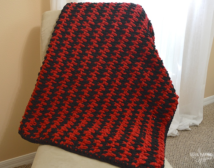 completed blanket in black and red hanging over a chair