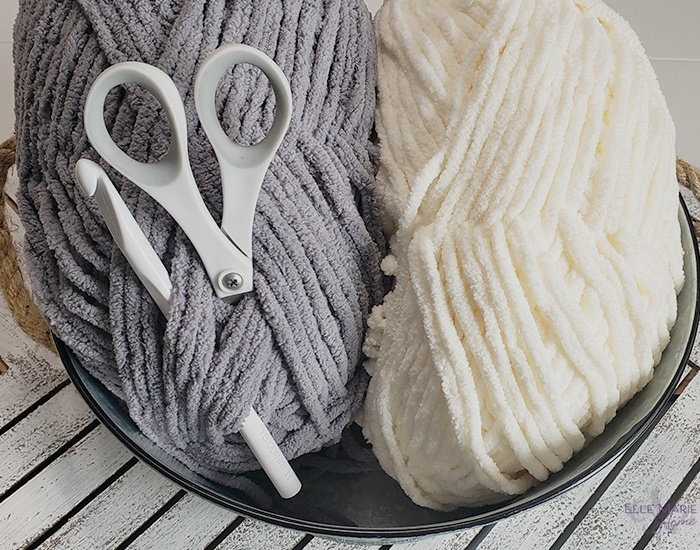 Linen Stitch Crochet Blanket yarn in gray and cream in a bucket with a crochet hook and scissors